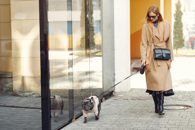 Mujer elegante con un abrigo marrón con bulldog negro