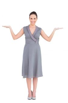 Mujer elegante alegre en vestido elegante posando manos arriba