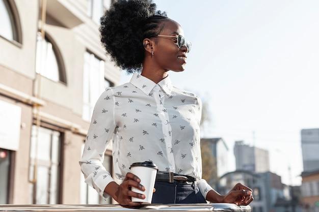 Mujer elegante de ángulo bajo con café en el balcón