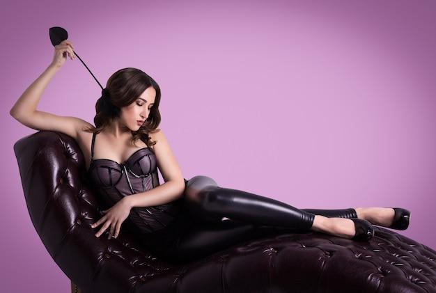 La mujer elegante atractiva miente en corsé en el sofá de cuero