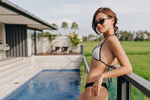 Mujer elegante y atractiva con traje de baño posando junto a una villa moderna con piscina azul y campo de arroz.