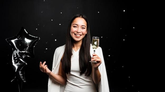 Mujer elegante brindando con champán y globos