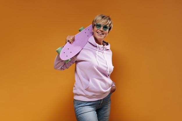 Mujer elegante de buen humor con peinado corto y gafas de sol verdes en una moderna sudadera con capucha y pantalones vaqueros frescos sonriendo y sosteniendo una patineta rosa.