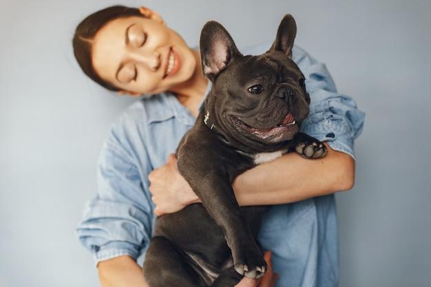 Mujer elegante en una camisa azul con bulldog negro