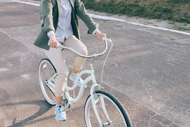 Mujer elegante en una camisa verde monta en la bicicleta de la ciudad en la carretera