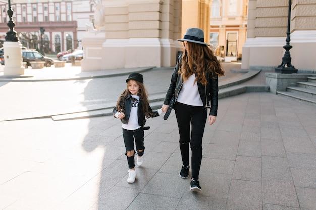 Mujer elegante delgada en jeans negros sosteniendo la mano de su linda hija en chaqueta de cuero, caminando por la calle.
