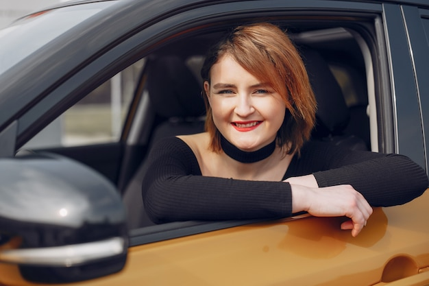 Mujer elegante y elegante en un salón de autos.