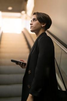 Mujer elegante en la escalera mecánica mirando a otro lado