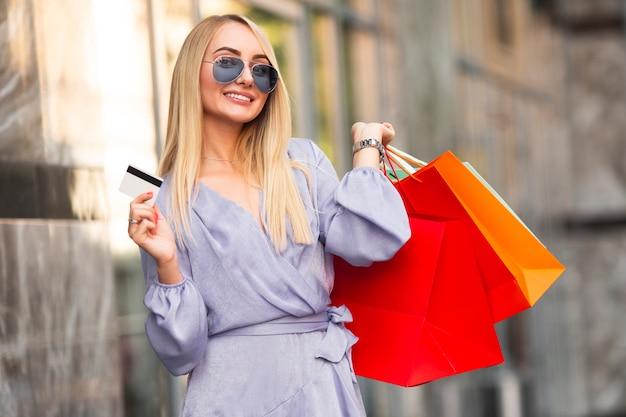 Mujer elegante y feliz con bolsas de compras