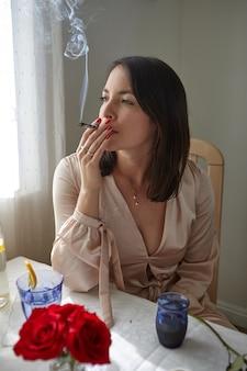 Mujer elegante fumando un porro en casa
