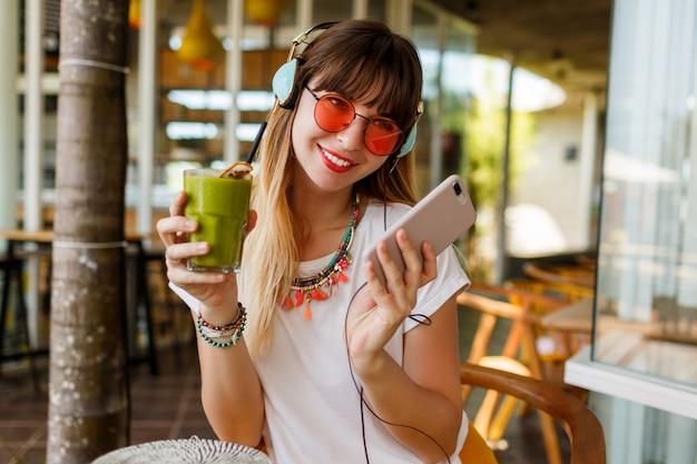 Mujer elegante en gafas de color rosa disfrutando de batido verde saludable, escuchando música por auriculares, sosteniendo el teléfono móvil.