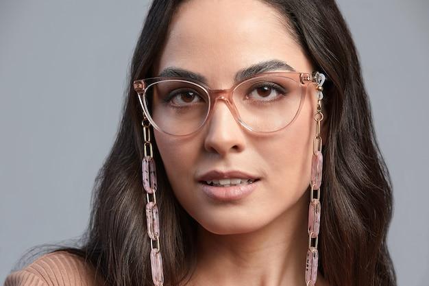Mujer elegante con gafas, retrato de moda de una mujer de negocios con gafas elegantes sobre un fondo gris, banner publicitario de gafas, espacio de copia