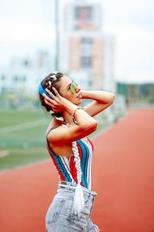 Una mujer elegante con gafas de sol y auriculares grandes escucha música en el estadio.