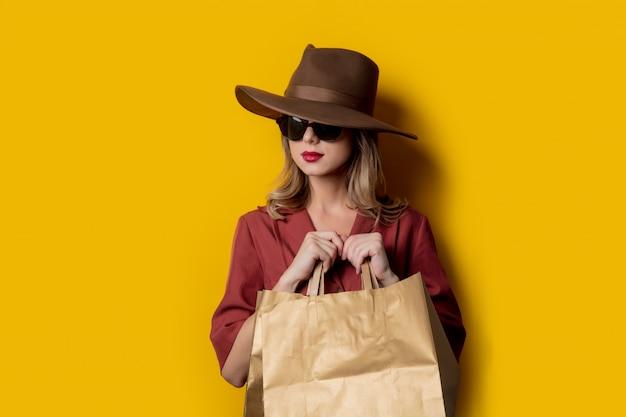 Mujer elegante en gafas de sol y con bolsas de compras
