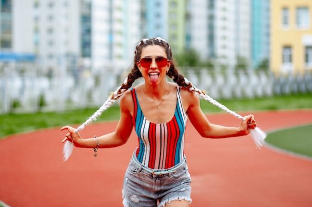 Una mujer elegante en gafas de sol posa alegremente en el contexto del estadio.