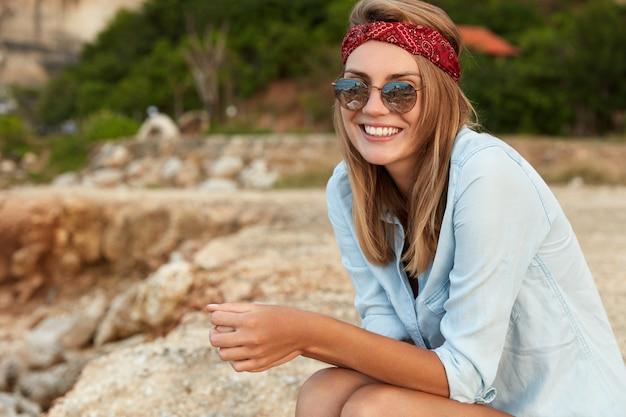 Mujer elegante con gafas de sol sentado en la playa