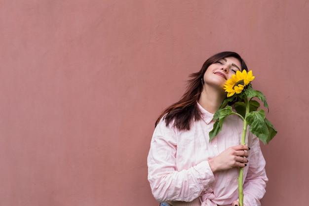 Mujer elegante con girasol en manos soñando alegremente