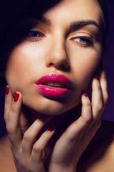 Mujer elegante glamour con labios rosados, uñas rojas y piel perfecta