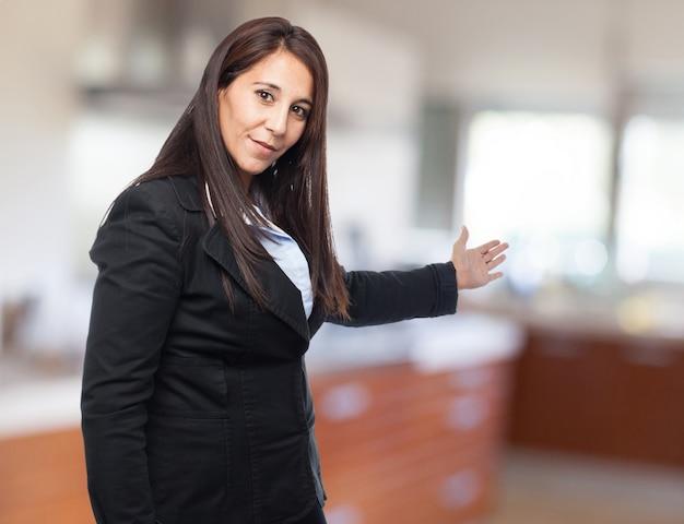 Mujer elegante invitando a entrar con una mano