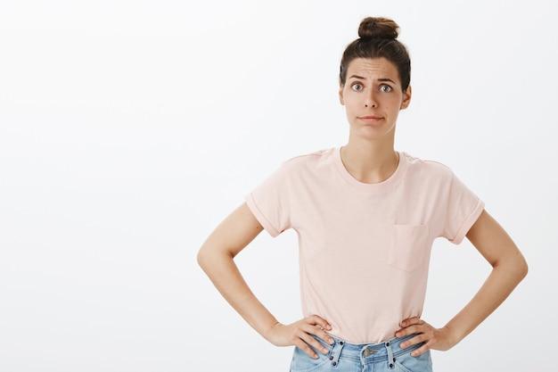 Mujer elegante joven confundida que presenta contra la pared blanca