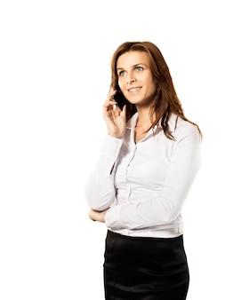 Mujer elegante joven hablando por teléfono móvil contra el fondo blanco.