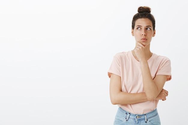 Mujer elegante joven pensativa posando contra la pared blanca