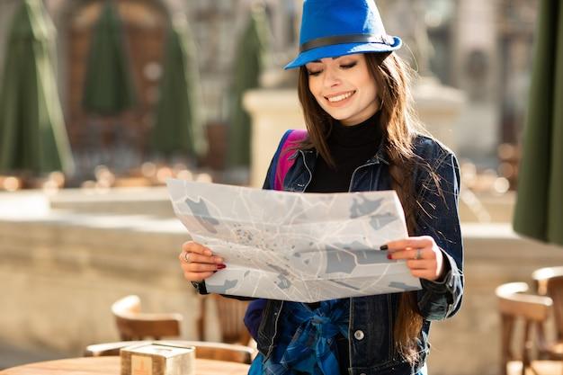 Mujer elegante joven que camina en la calle vieja de la ciudad, viaje con la mochila y el sombrero azul. ucrania, lviv