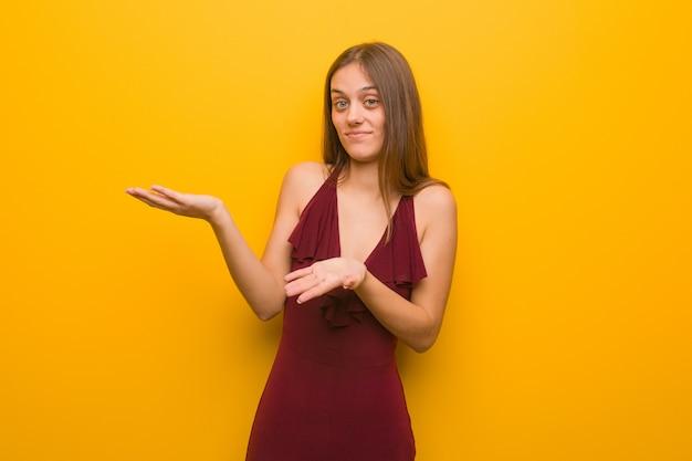 Mujer elegante joven que lleva un vestido confundido y dudoso