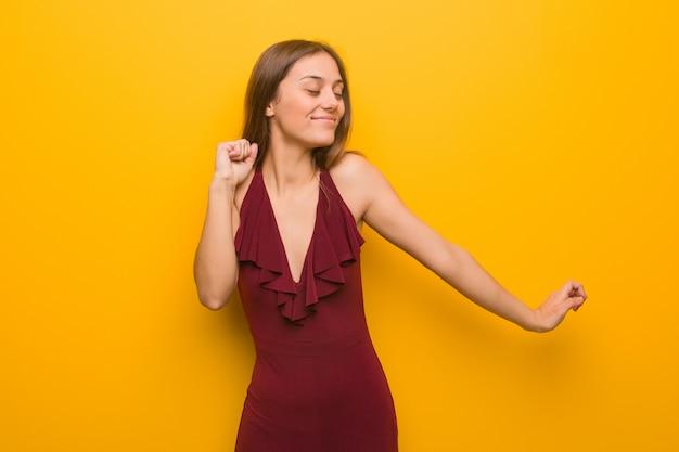 Mujer elegante joven que lleva un vestido que baila y que se divierte