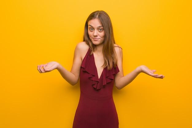 Mujer elegante joven que lleva un vestido que duda y que encoge hombros