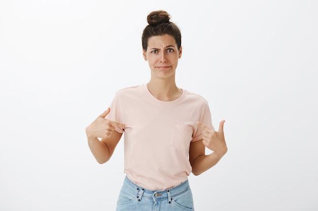Mujer elegante joven reacia y disgustada posando contra la pared blanca