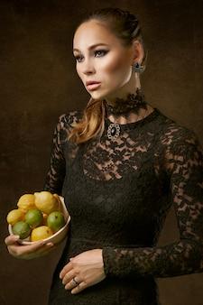 Mujer elegante con limones y limas