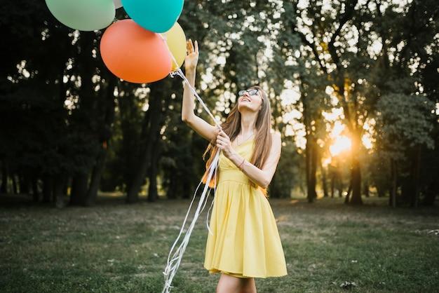 Mujer elegante en la luz del sol mirando globos
