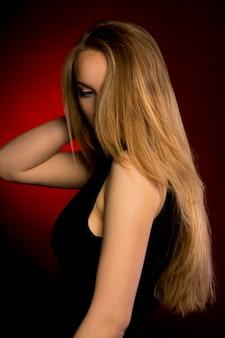 Mujer elegante con maquillaje natural y exuberante cabello rubio en el estudio
