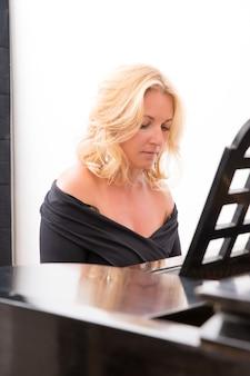 Mujer elegante músico clásico tocando el piano.