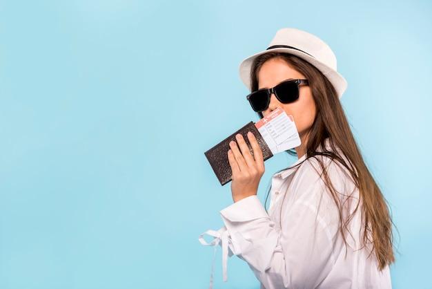 Mujer elegante con pasaporte y entradas.
