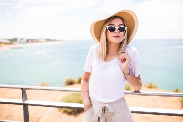Mujer elegante en la playa de verano en un día caluroso con sombrero de verano y gafas de sol