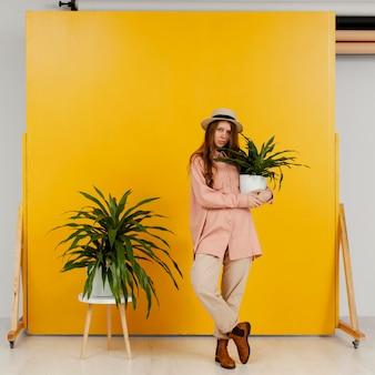 Mujer elegante posando con macetas de plantas