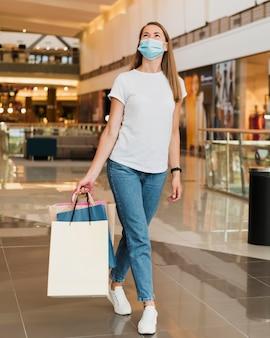 Mujer elegante, proceso de llevar, bolsas de compras