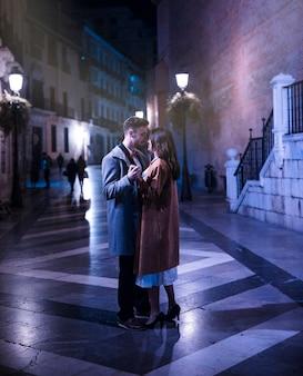 Mujer elegante que abraza con el hombre joven en la calle por la tarde