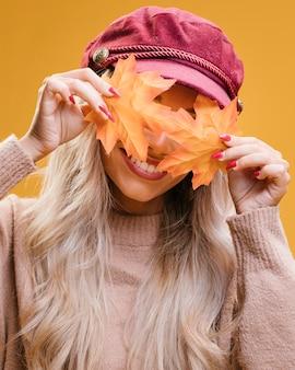 Mujer elegante que cubre sus ojos con hojas de otoño