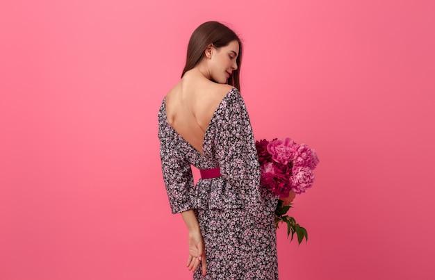 Mujer elegante en rosa en vestido de moda de verano posando con ramo de flores de peonía, vista desde atrás