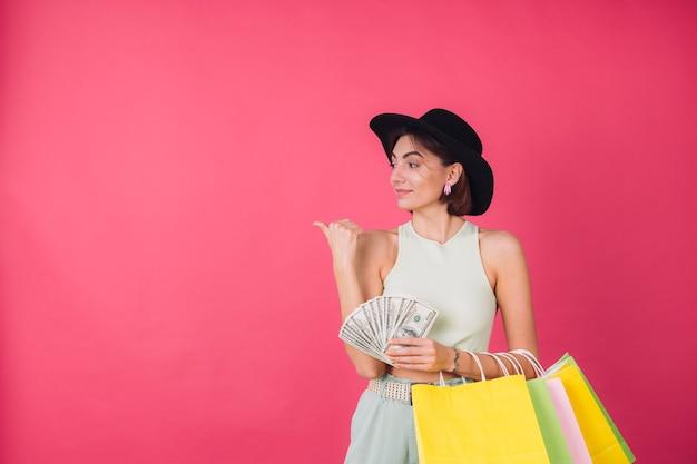 Mujer elegante con sombrero en la pared roja rosa