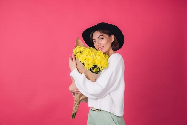 Mujer elegante con sombrero en la pared roja
