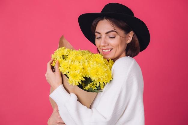 Mujer elegante con sombrero en la pared roja Foto gratis