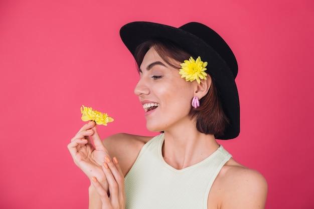 Mujer elegante con sombrero, sonriendo con dos ásteres amarillos, humor primaveral, espacio aislado de emociones felices