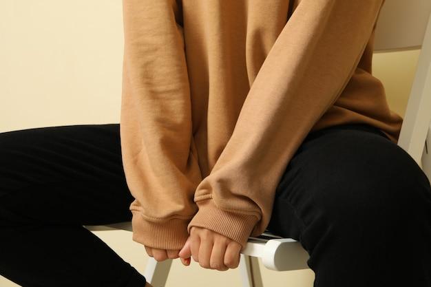 Mujer con elegante sudadera sentada en una silla
