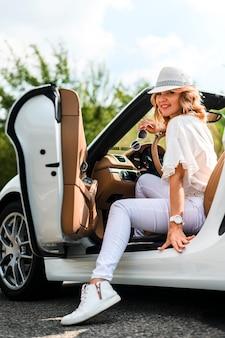 Mujer elegante en tiro completo del coche
