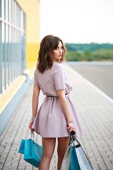 Mujer elegante en un tour de compras en la ciudad llevando artículos comprados en bolsas de papel