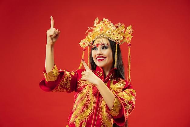 Mujer elegante tradicional china en el estudio sobre fondo rojo. hermosa chica vestida con traje nacional. año nuevo chino, elegancia, gracia, ejecutante, actuación, danza, actriz, concepto de vestimenta